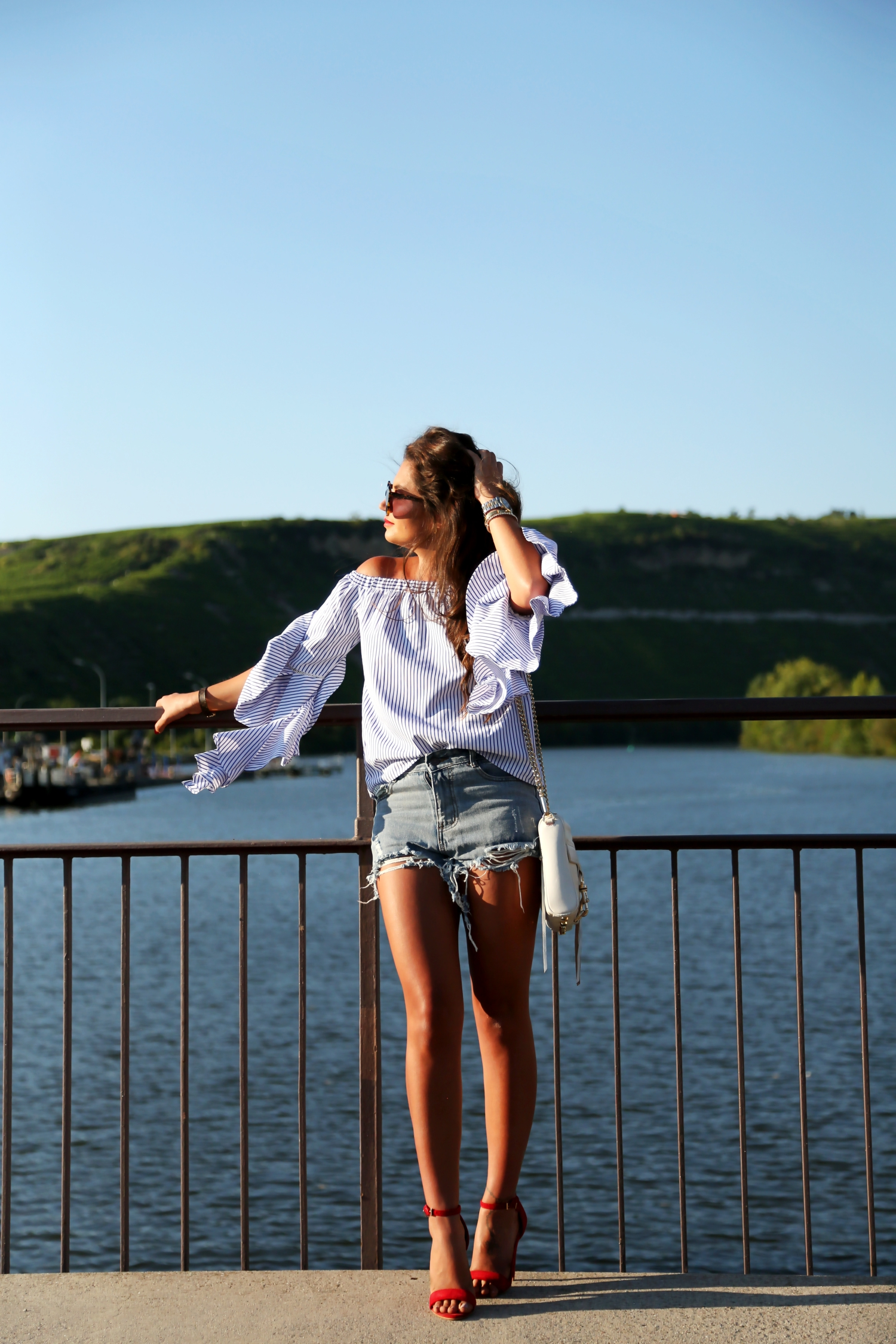 outfit-ripped-denim-shorts-off-shoulder-top-mac-clutch-red-sandals